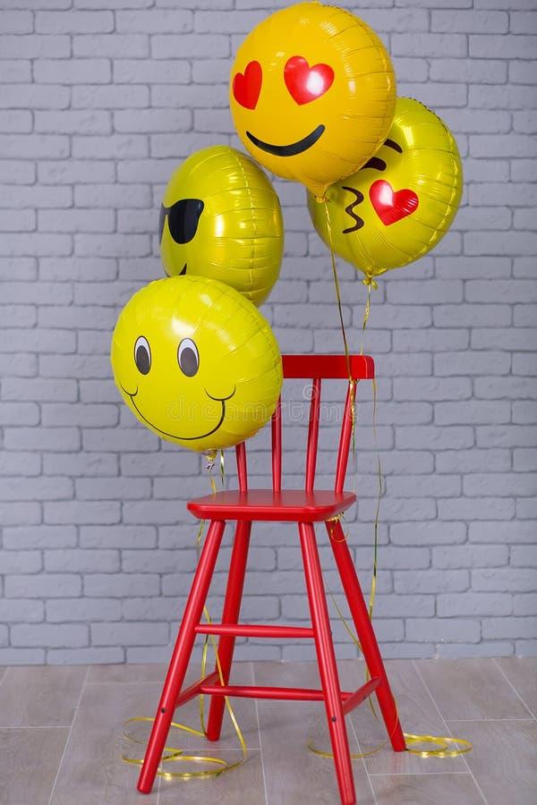 Popielaty mieszkania studio z krzesłem, ściana z cegieł, kolorów żółtych szczegóły szybko się zwiększać emoji czerwonego krzesła zdjęcie royalty free