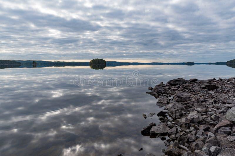 Popielaty niebo odbija w spokój wodzie w jeziorze fotografia stock