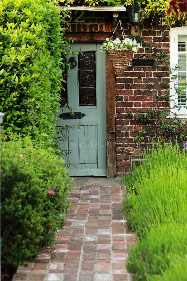 Popielaty Stary drzwi Z Pomarańczowym Bricky ściany i zieleni lawendy ogródem zdjęcia stock