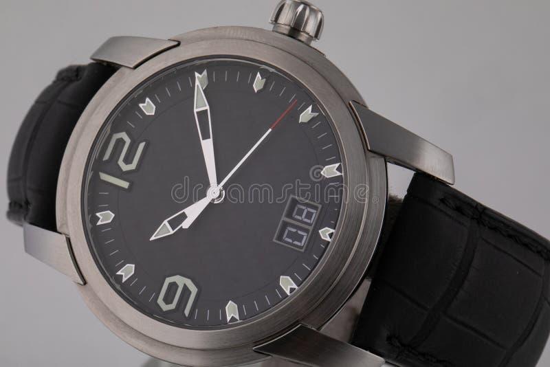 Popielaty wristwatch z czarną tarczą, osrebrza clockwise, i chronograf na czarnej rzemiennej patce odizolowywającej na białym tle zdjęcia royalty free