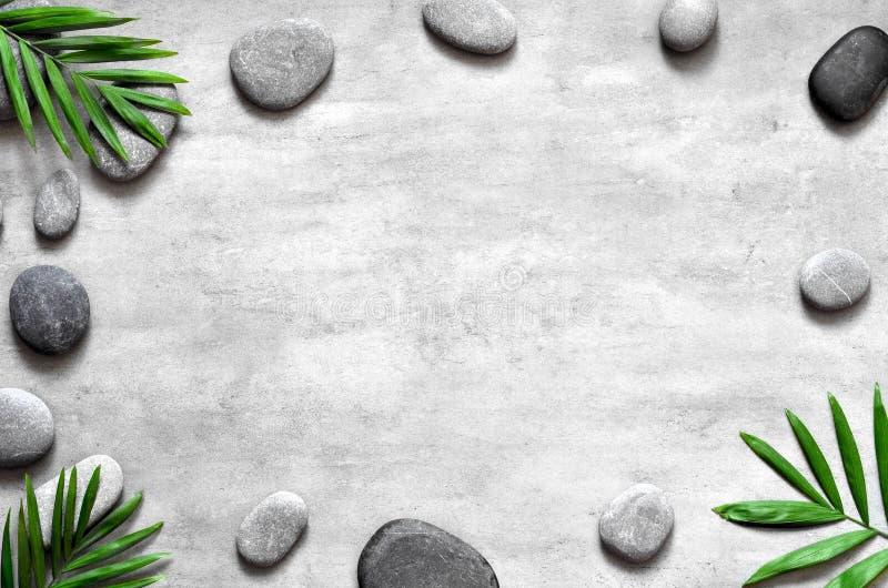 Popielaty zdroju tło, palma liście, i siwiejemy kamienie, odgórny widok obraz stock