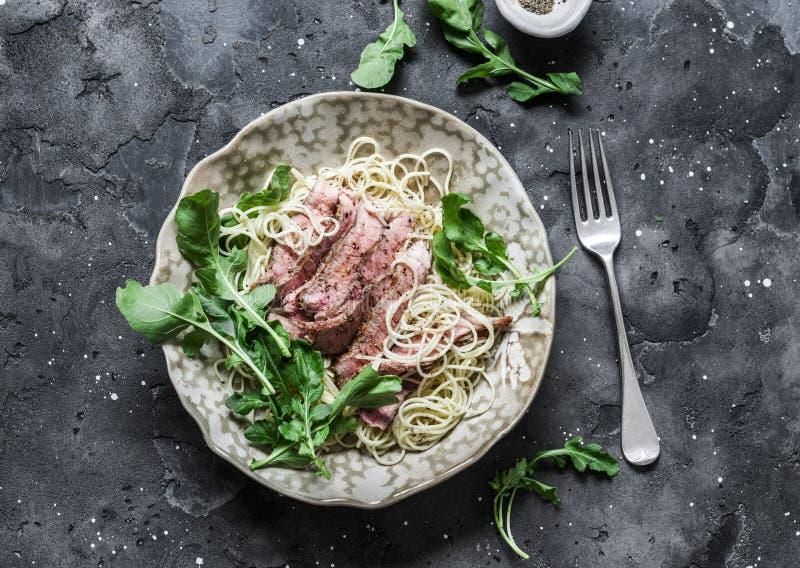 Popieprzony stku makaron Spaghetti makaron z pokrojonym wołowina stkiem i rakietową sałatką na ciemnym tle, odgórny widok zdjęcia stock