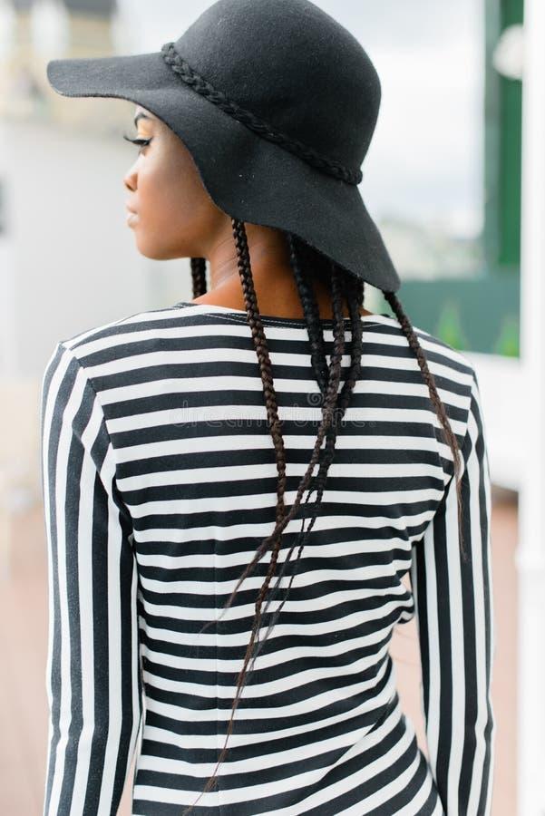 Popiera afrykanina model, będący ubranym czarnego kapelusz i pasiastego kapelusz obrazy royalty free