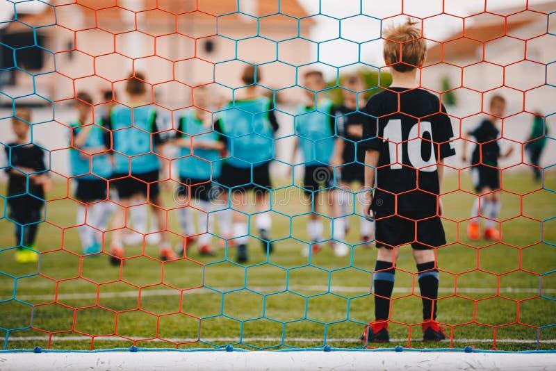 Popiera dziecka gracz futbolu Młoda chłopiec pozycja w Futbolowym celu Niskiego kąta wizerunek Za od Bramkowej sieci fotografia stock