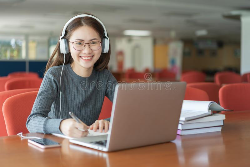 Popiera edukaci szkolnej wiedzy szkoły wyższa uniwersytecki pojęcie, Piękny uśmiechnięty żeński uczeń używa online edukaci usługa fotografia royalty free