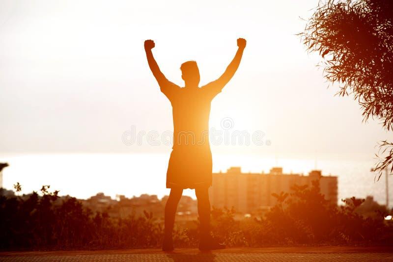 Popiera mężczyzna pozycja zmierzchem z rękami podnosić zdjęcia royalty free