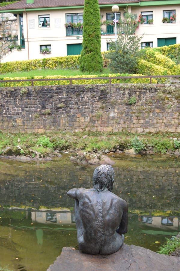Popiera mężczyzna statuy ryba Obok Uroczego rzymianina mostu W Lierganes Sierpie? 24, 2013 Lierganes, Cantabria Urlopowa natura obrazy royalty free