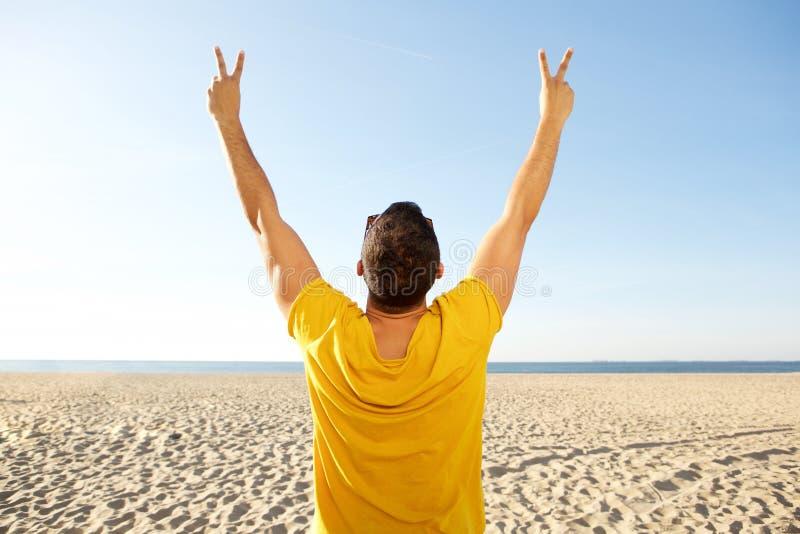 Popiera mężczyzny doping z rękami podnosić przy plażą fotografia stock