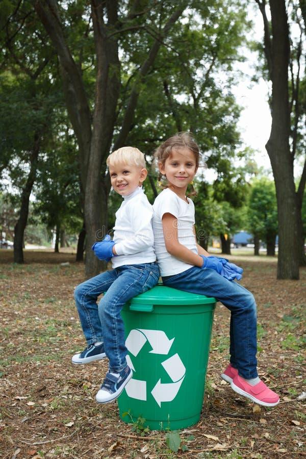 Popiera popierać dzieci w cajgach i biel skróty, siedzi na dużej zieleni przetwarzają kosz z białą etykietką na przodzie obrazy stock