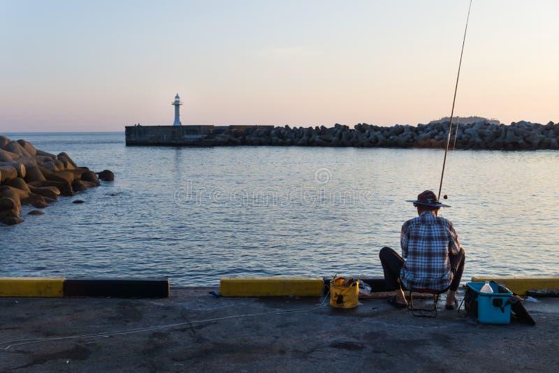 Popiera rybak przy schronieniem z białą latarnią morską podczas zmierzchu, Seogwipo, Jeju wyspa, Południowy Korea fotografia royalty free