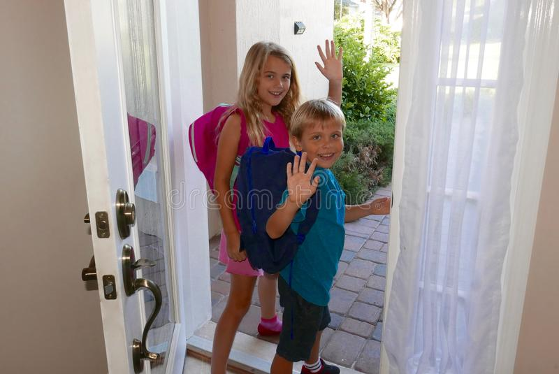 Popiera szkoła: Dziewczyna i chłopiec chodzący out dzwi wejściowy zdjęcia stock