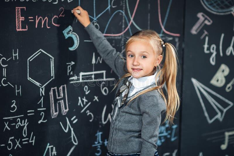 Popiera szkoła! Dziewczyna rysunek na pustym chalkboard z szkolnymi formułami przy szkołą Dzieciak studiuje w sali lekcyjnej na fotografia royalty free