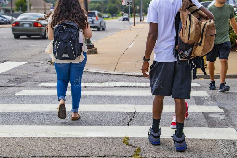 Popiera szkoła etniczna różnorodność i przypadkowa suknia z ca - plecy studenci collegu krzyżuje miastowego crosswalk z plecakami obrazy stock