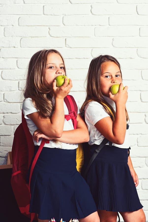 Popiera szkoła i szczęśliwego czasu Śliczni dzieci je jabłka Dzieciaki uczą się w klasie na tle ściana z cegieł obraz royalty free