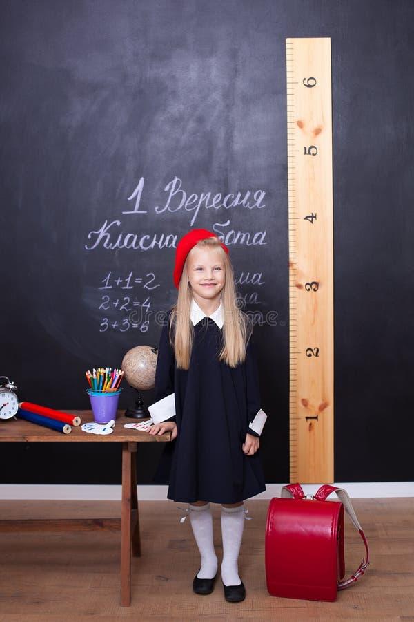 Popiera szkoła! mała dziewczynka przy szkołą stoi blisko stołu czarnych t?a poj?cia do copyspace ksi??ek Uczennica odpowiada lekc obrazy royalty free
