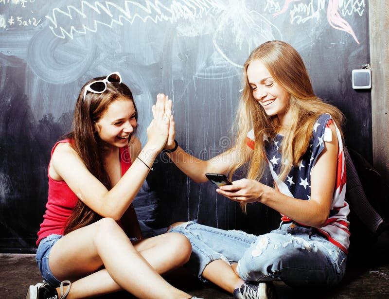 Popiera szkoła po wakacji, dwa nastoletniej istnej dziewczyny w sala lekcyjnej z blackboard malującym wpólnie zdjęcia royalty free
