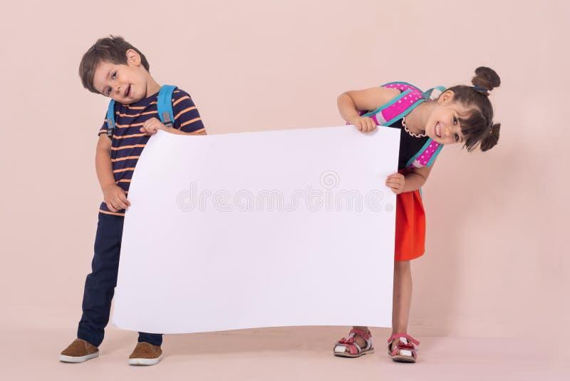 Popiera szkoła - reklamy Szkoła dzieciaki trzyma białą pustego miejsca lub bielu kartę z plecakami zdjęcie royalty free