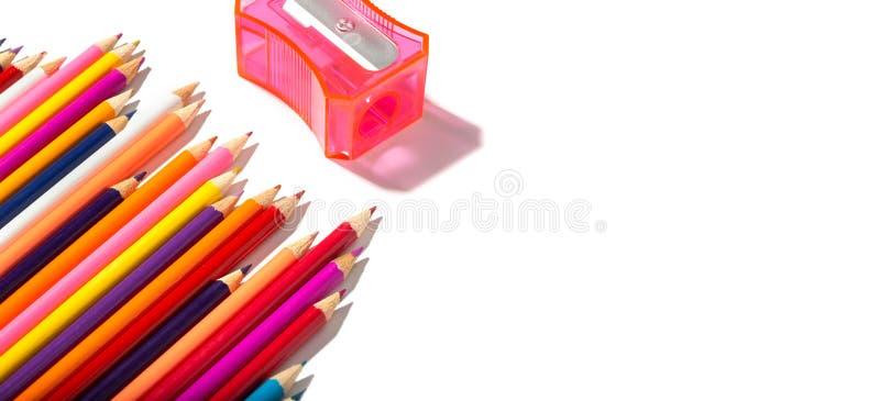 Popiera szkoła sztandar stubarwni ołówki i ołówkowa ostrzarka odizolowywający na białym tle zdjęcia royalty free