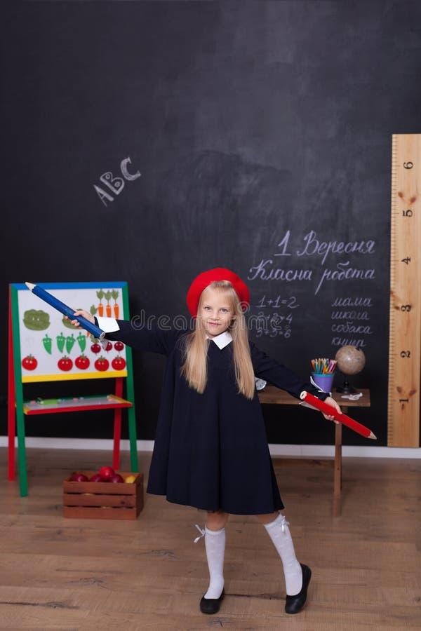 Popiera szkoła! Troszkę dziewczyna stojaki z wielkimi ołówkami w jej rękach przy szkołą Uczennica odpowiada lekcja Dzieciak jest  obraz royalty free