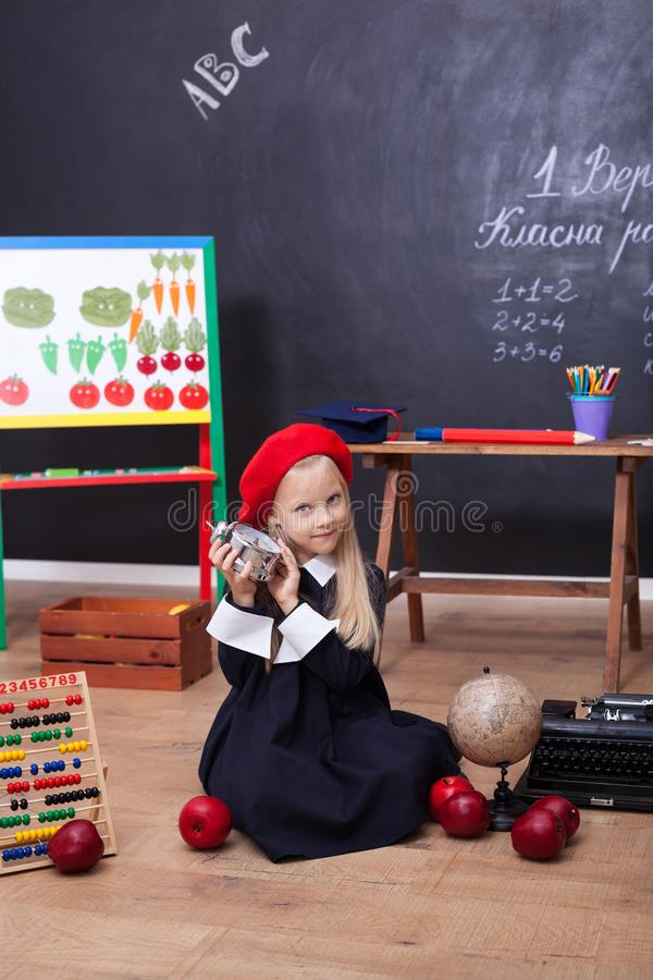 Popiera szkoła! Troszkę siedzi w lekcji z zegarem w ona ręki dziewczyna Uczennica odpowiada lekcja Dzieciak jest mną studiujący obrazy royalty free
