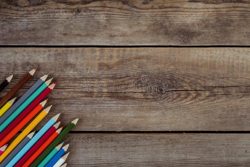 Popiera szkoły pojęcia tło z barwionymi ołówkami na drewnianym stole, mieszkanie nieatutowy zdjęcia royalty free