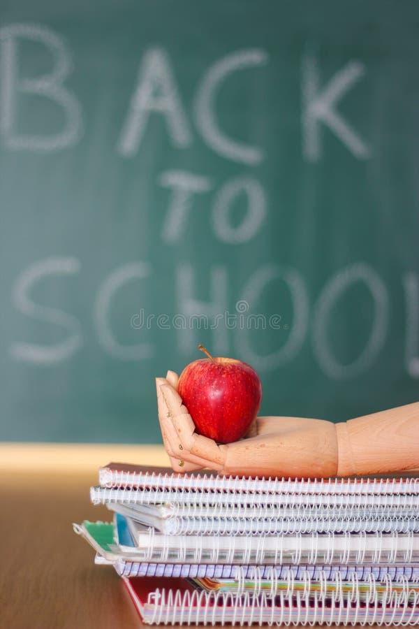 Popiera szko?y t?o z drewnian? r?k? trzyma jab?ka i notatnik?w zdjęcie stock