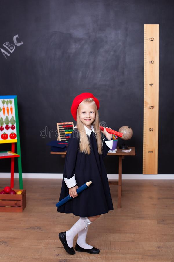 Popiera szko?a! Troszk? dziewczyna stojaki z wielkimi o??wkami w jej r?kach przy szko?? Szkolna dziewczyna odpowiada lekcja Dziec fotografia stock