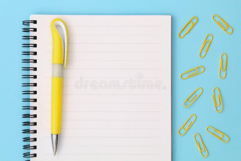 Popiera szko?y kreatywnie poj?cie Notepad z żółtym piórem i klamerki na błękitnym tle Odg?rny widok p?aski k?a?? fotografia stock