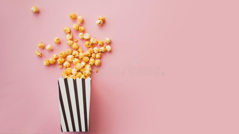Popkorn w papierowej torbie rozpraszał na różowego tła odgórnym widoku obrazy stock