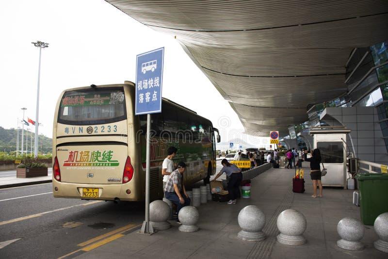 Popolo cinese che determina la fermata dell'autobus per l'invio dei passeggeri alla parte anteriore dell'aeroporto internazionale immagine stock