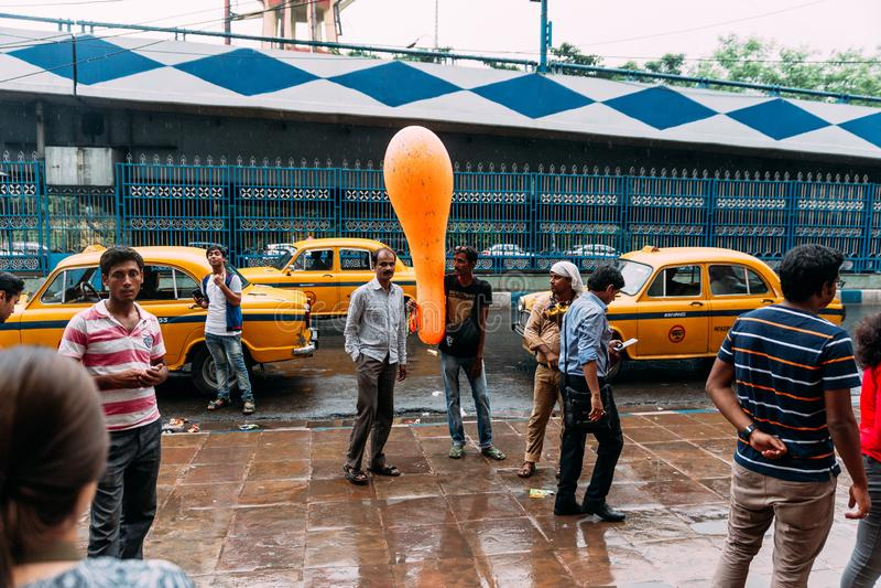 Popolo indiano che aspetta davanti al museo indiano la vendita del pallone arancio del questionario lungo con i taxi gialli sulla immagini stock libere da diritti