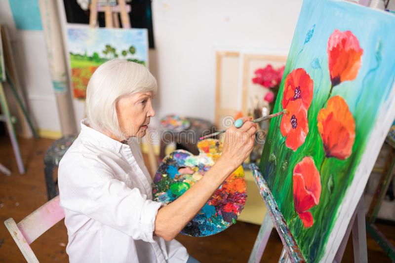 Blonde-haired woman painting red poppies on canvas royalty free stock photo