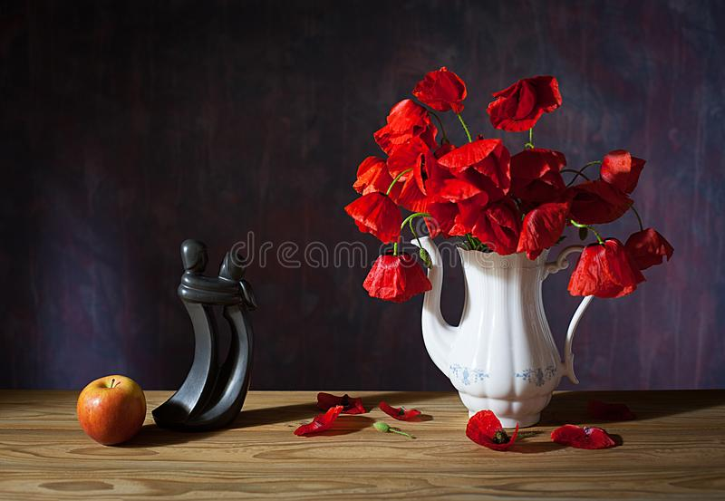 Poppies in a vase, books and apple stock image