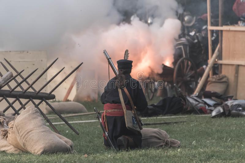 Pop off moment of a historical cannon with a soldier. Popping off a historical cannon during battle reconstruction in a park stock images