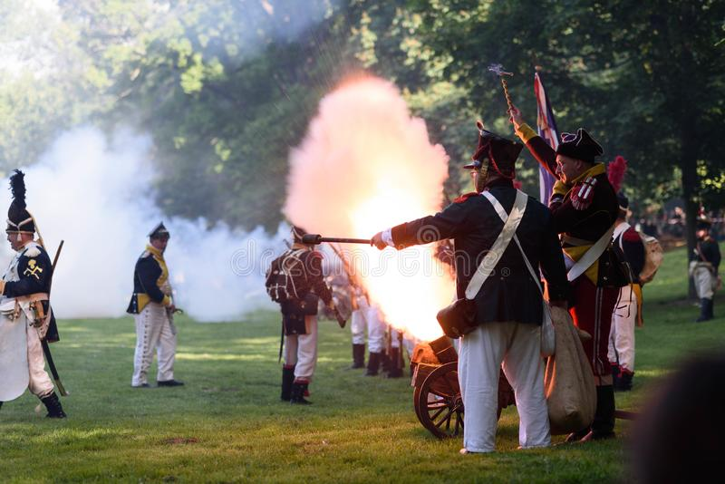 Pop off moment of a historical cannon with soldiers. Popping off a historical cannon during battle reconstruction in a park stock image