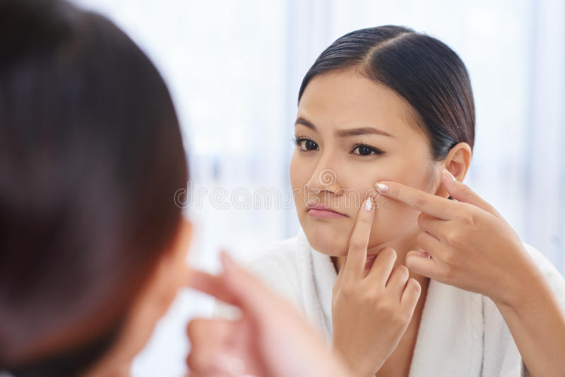 Popping pimple. Unhappy beautiful Asian woman popping pimple on her cheek royalty free stock photo