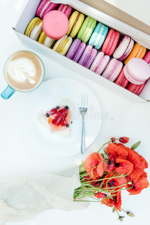 Poppy flowers bouquet and french macarons with tasty cake and cappuccino on white table royalty free stock photo