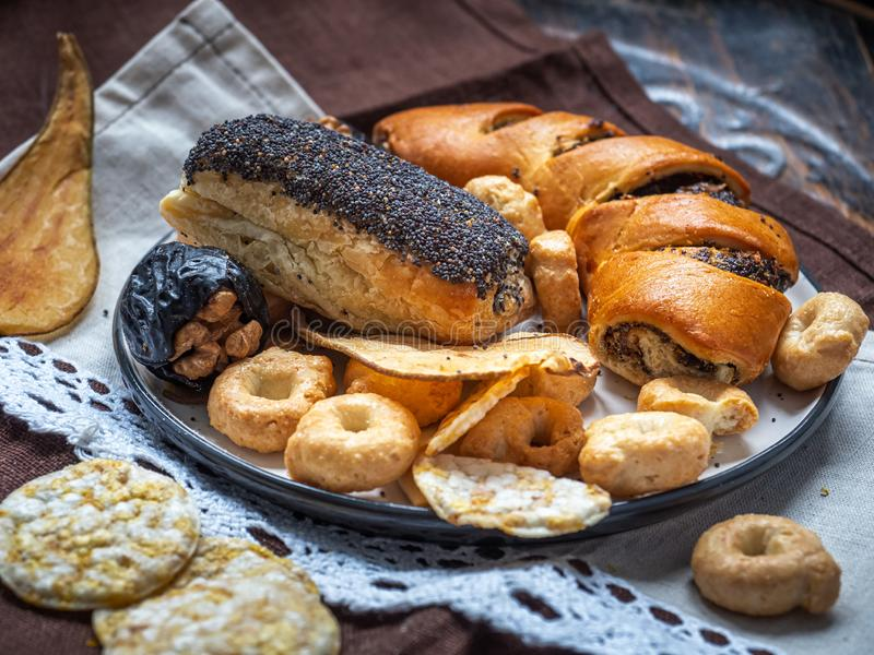 Poppy pastries, cookies and fruit, cereal chips for dessert, tasty lunch, closeup shot on a cotton napkin stock photos