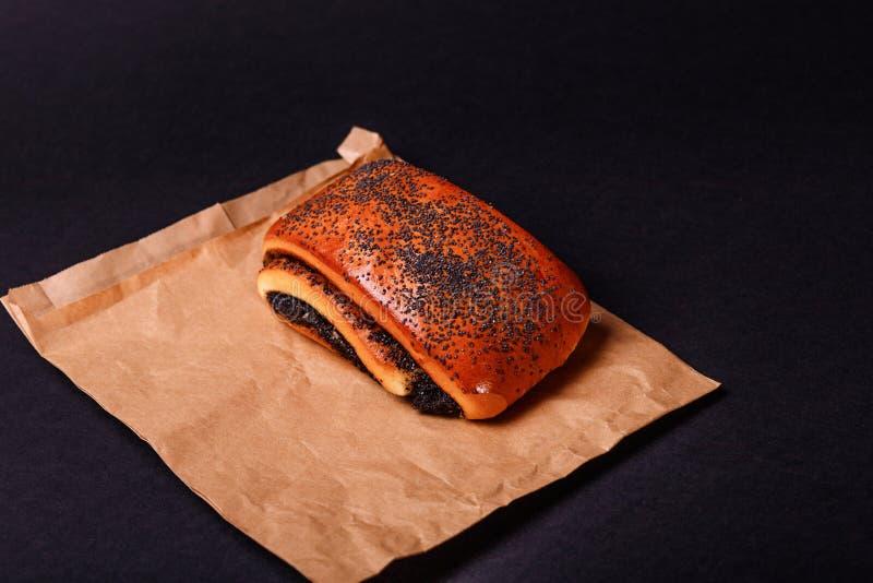 Poppy roll on black background. Tasty bake royalty free stock images