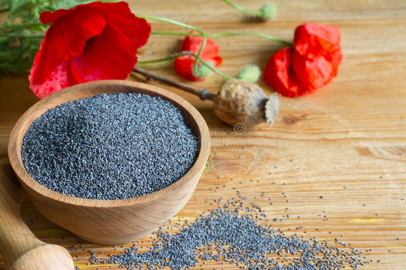 Poppy seed and flowers on the table. Art stock images