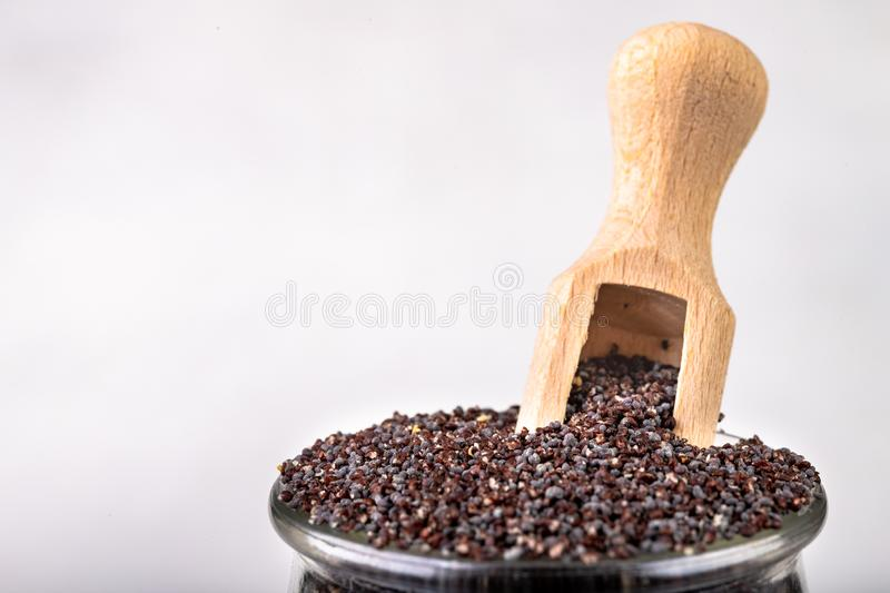 Poppy seed on the kitchen table. Spilled poppy seed and wooden spoon royalty free stock photo