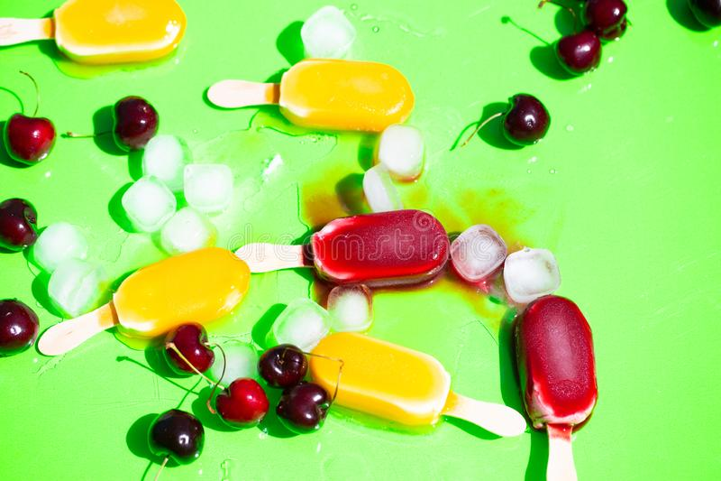 Popsicles, που βρωμίζεται με τα κεράσια και τους κύβους πάγου στοκ εικόνα