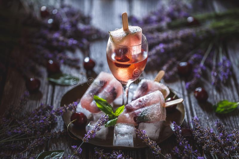Popsicles Cocktail. With wine, cherry, lavender and basil stock images