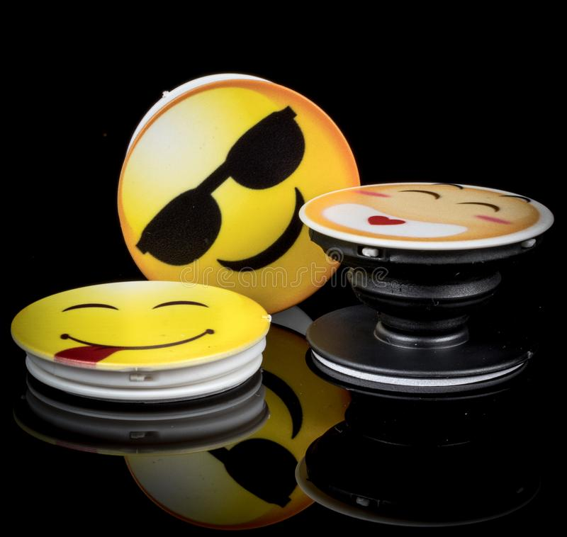 Popsockets with Emoji pictures on black background stock photography