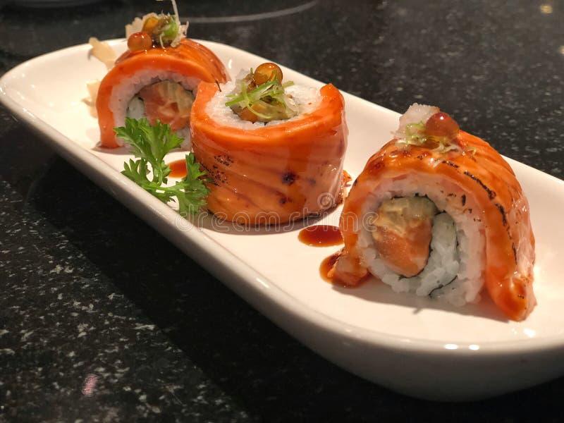 populär japansk mat Grillade Salmon Sushi Rolls i den vita plattan royaltyfri fotografi