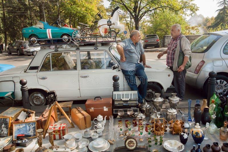 Populäre Flohmarkt trockene Brücke und zwei Verkäufer, die über Geschäft, Weinleseautos, altes Personal, Andenken sprechen lizenzfreie stockfotografie