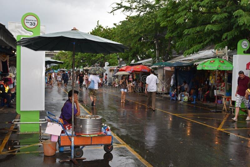 Populärer Chatuchak-Wochenenden-Markt während der Regenzeit mit den Besuchern, die Regenschirme halten stockfotos