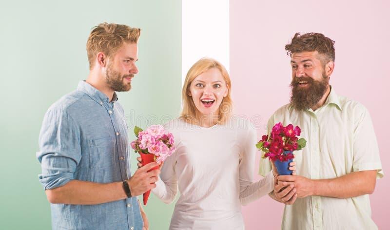 Populaire het meisje krijgt de aandacht van partijmensen Vrouw het glimlachen kan geen partner kiezen, grijpt beide boeketten Gel royalty-vrije stock fotografie