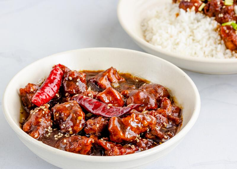 Popular American-Chinese Takeout Food General Tso`s Chicken with Rice in a Bowl. General Tso`s chicken on Top of Rice in a Bowl Garnished with Sesame Seeds and stock photo