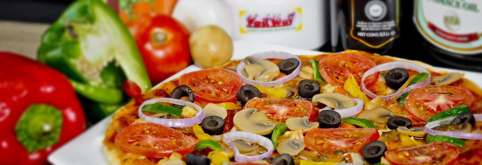 Popular colorful ingredients as like tomatoes, cheese, mushroom, capsicum, olives and other ingredients baked healthy Pizza.  stock photo